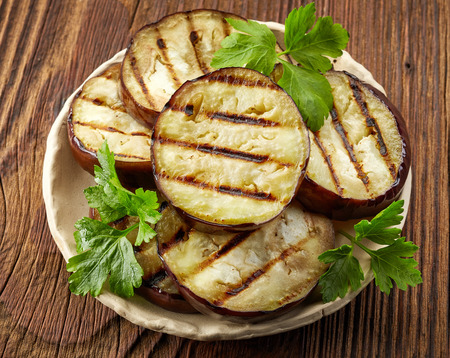 52935745 - grilled eggplant slices and green parsley on wooden table